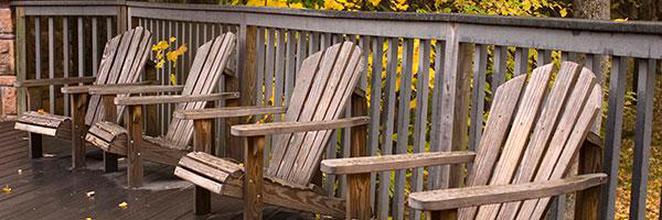 Adirondack chairs sit outside 克拉克森大学's Adirondack Lodge on campus