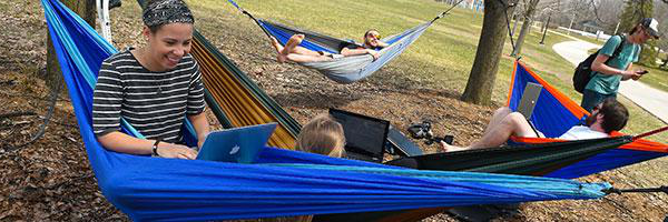 克拉克森大学 undergraduate students relax in a hammock on the Cheel Lawn in spring.